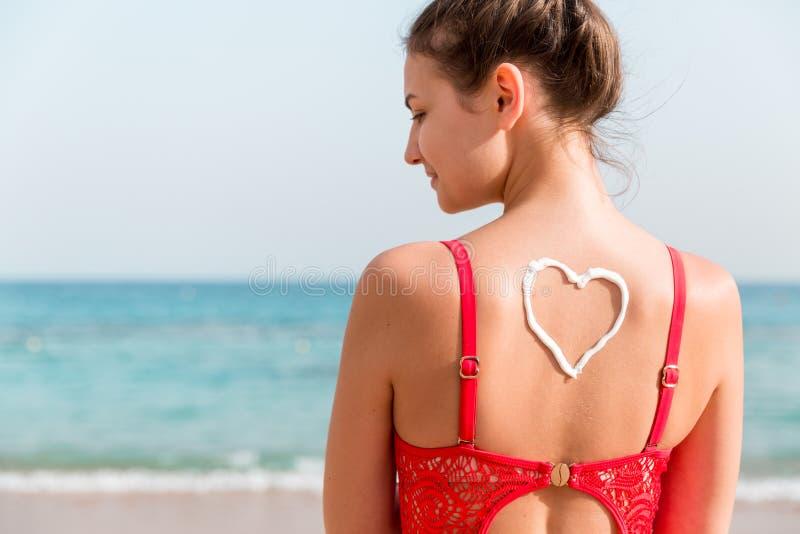 La belle fille dans le maillot de bain rouge a le sunblock dans la forme du coeur au fond à la plage photographie stock libre de droits
