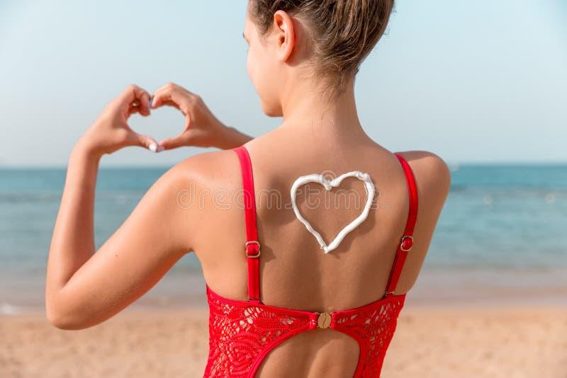 La belle fille dans le maillot de bain rouge a le sunblock dans la forme du coeur au fond ? la plage photographie stock