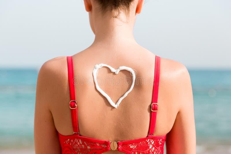 La belle fille dans le maillot de bain rouge a le sunblock dans la forme du coeur au fond ? la plage images stock