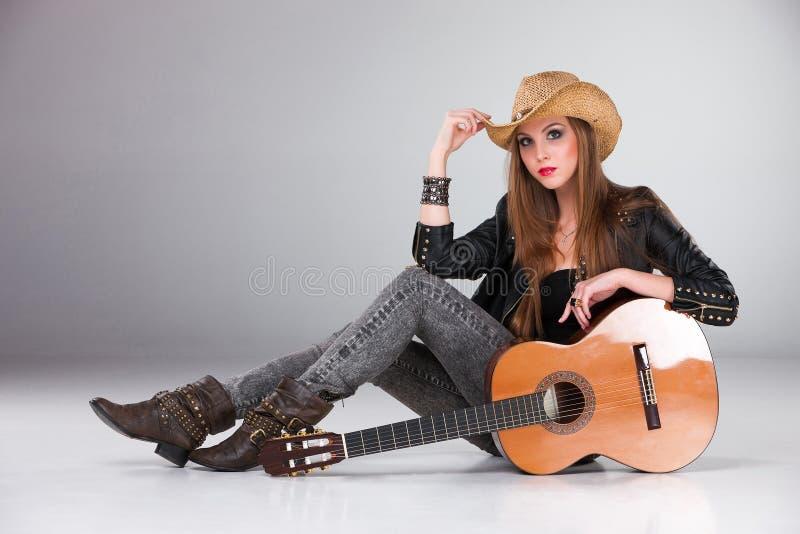 La belle fille dans un chapeau de cowboy et acoustique photographie stock