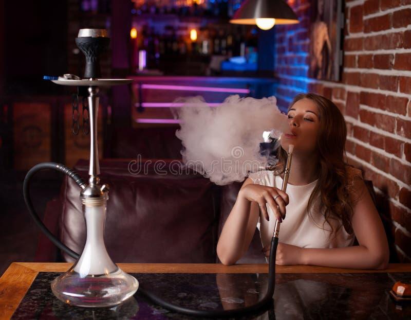 La belle fille dans un chemisier blanc fume un narguilé à l'intérieur de la barre photos stock