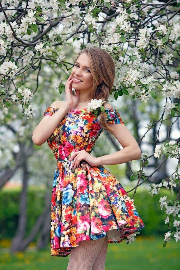 La belle fille dans une robe lumineuse, se tient contre les couleurs de fond photos stock