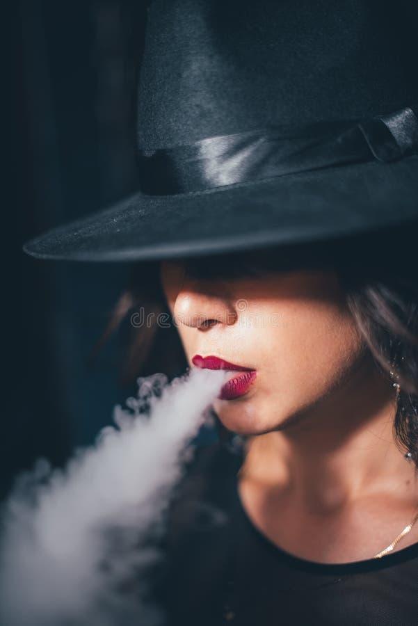 La belle fille dans une robe noire fume le narguilé sur des chaînes de fond image stock