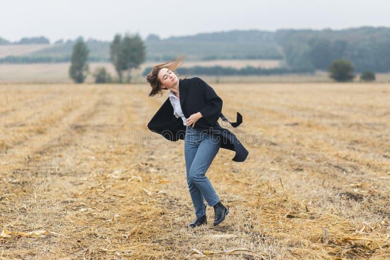 La belle fille danse dehors dans le domaine au temps nuageux d'automne image libre de droits