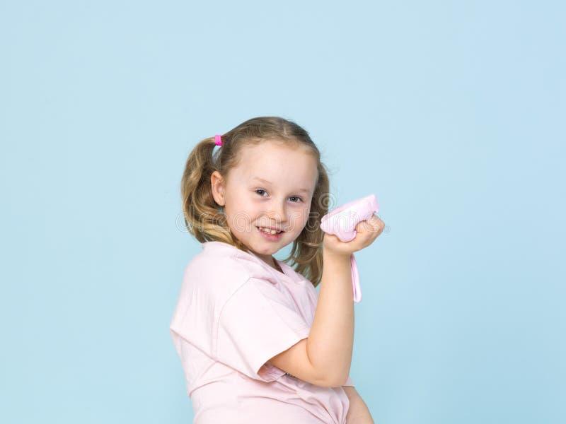 La belle fille de 8 ans joue avec la boue rose devant le fond bleu images stock