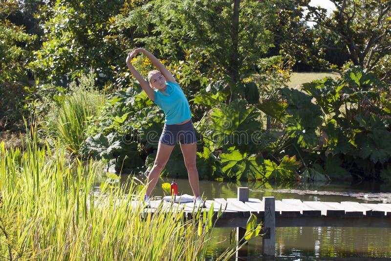 La belle fille de forme physique avec le sport d'été court-circuite étirer ses bras image stock