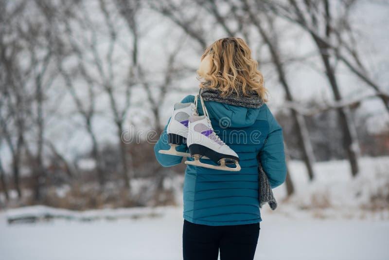 La belle fille de jeune femme avec des patins de glace vont à la piste image libre de droits