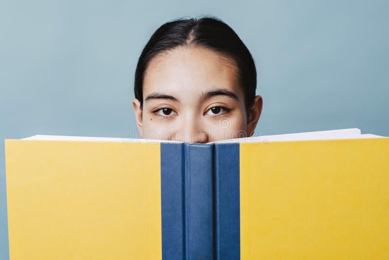 La belle fille de l'adolescence cache son sourire derrière un manuel heureux photos libres de droits