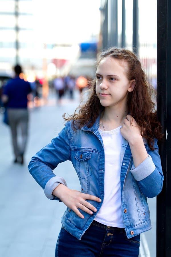 La belle fille de l'adolescence dans des vêtements de denim se tient se penchante sur un bâtiment en verre sur la rue de ville photo libre de droits