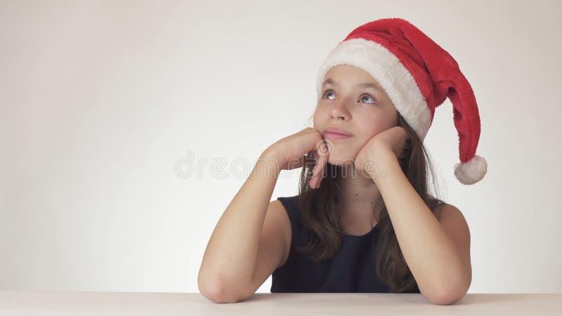 La belle fille de l'adolescence séance de chapeau de Santa Claus et en rêvant d'un cadeau, exprime le bonheur et l'anticipation s photo stock