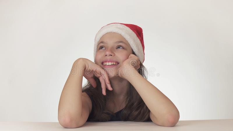 La belle fille de l'adolescence séance de chapeau de Santa Claus et en rêvant d'un cadeau, exprime le bonheur et l'anticipation s photographie stock libre de droits