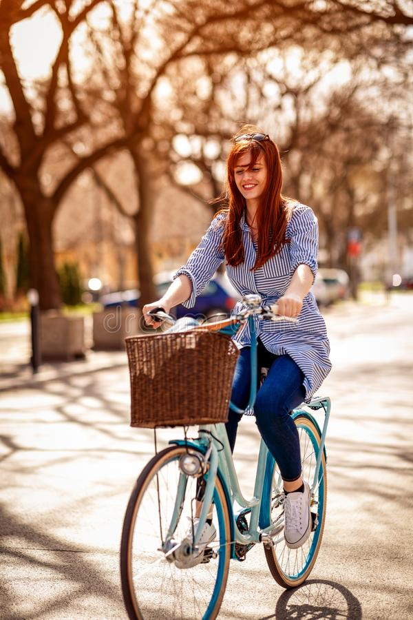 La belle fille de sourire monte la bicyclette en parc image libre de droits