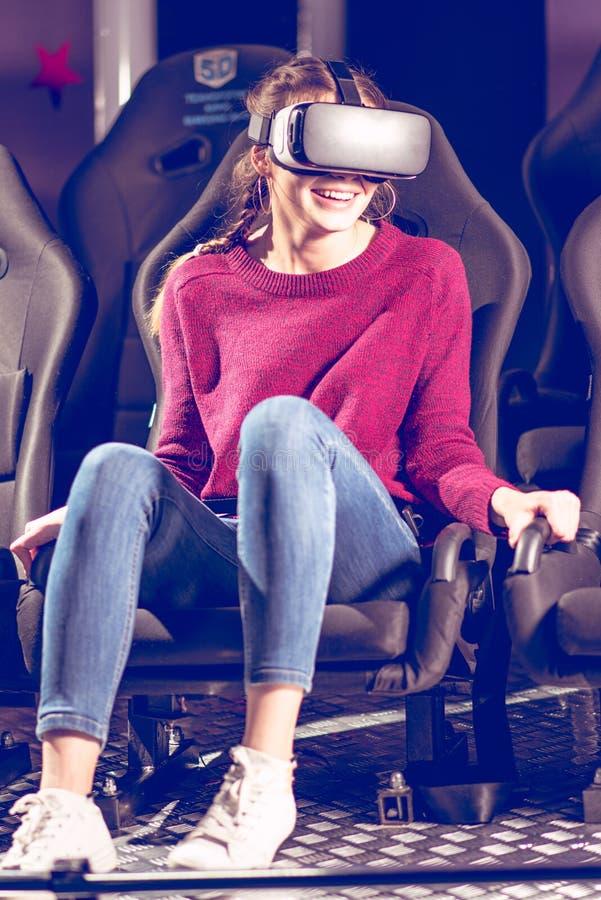 La belle fille en verres virtuels observe un film avec des effets spéciaux en 5d photographie stock