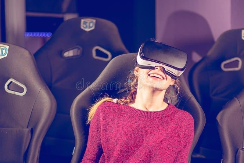 La belle fille en verres virtuels observe un film avec des effets spéciaux en 5d image libre de droits