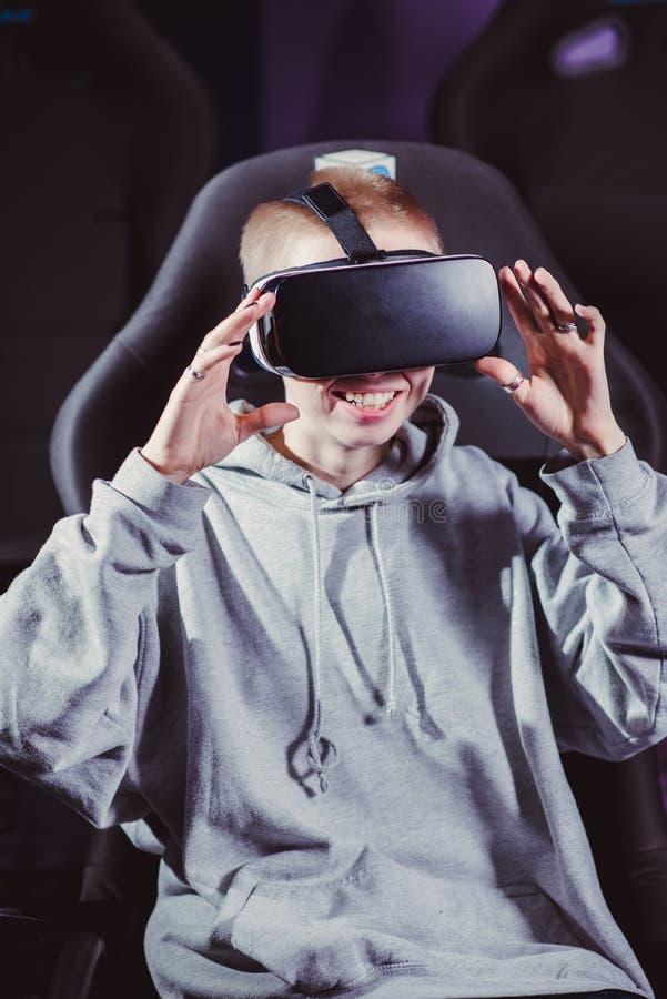 La belle fille en verres virtuels observe un film avec le speci photographie stock