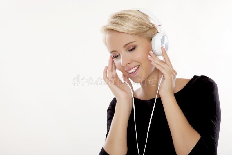 La belle fille est écoutent la musique images stock