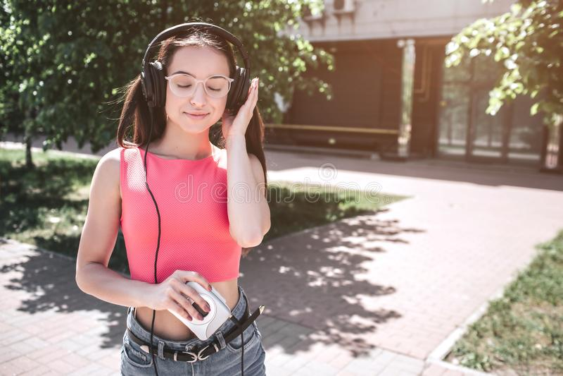 La belle fille est extérieure debout et écouter la musique dans des écouteurs Elle tient le petit et blanc joueur dans la droite photographie stock libre de droits