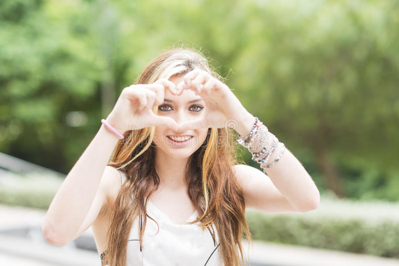La belle fille gaie avec le signe de coeur, le sentiment et l'émotion escroquent photographie stock