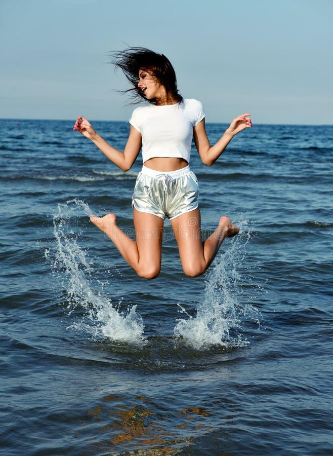 La belle fille heureuse sautent dans l'eau de mer image stock