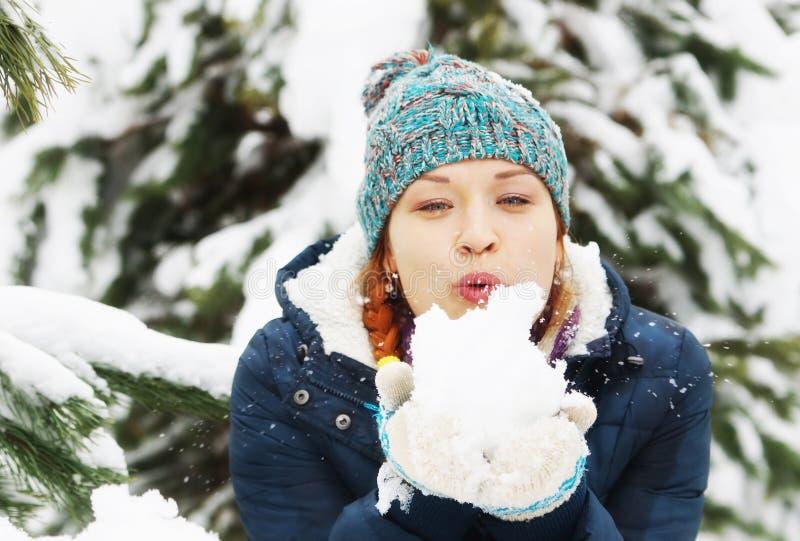 La belle fille heureuse souffle à la neige dans la forêt d'hiver photo libre de droits