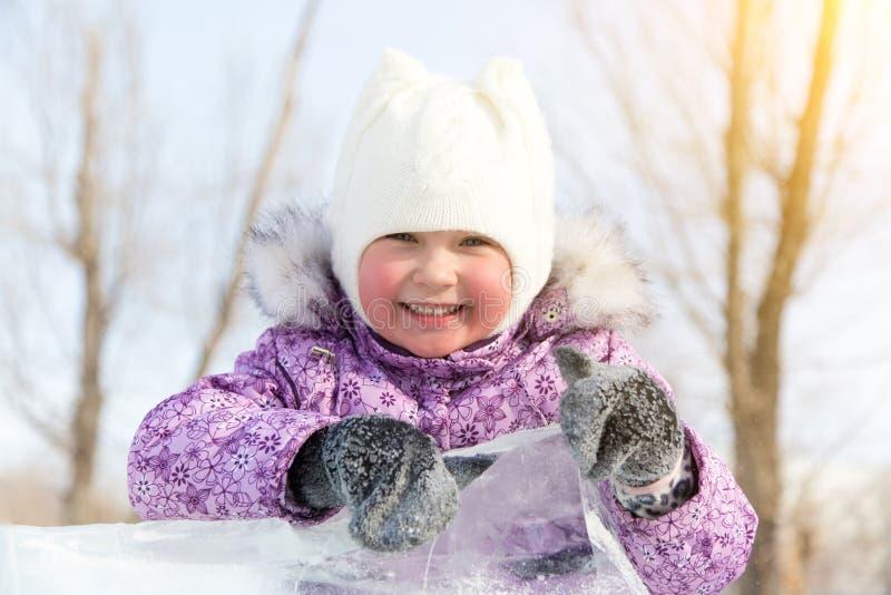La belle fille jette un coup d'oeil par derrière une pile de glace image libre de droits