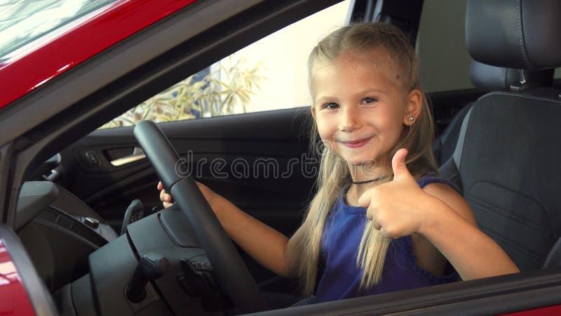 La belle fille mignonne fait tourner le volant d'une voiture photos libres de droits