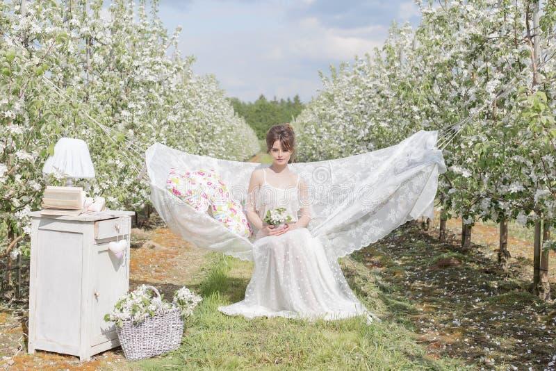 La belle fille mignonne sexy dans une robe blanche légère dans le jardin de floraison de pomme voit sur l'hamac avec un livre images stock