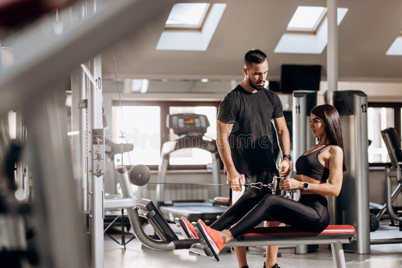La belle fille mince habillée dans des vêtements noirs de sport fait des exercices pour les abdominals sur une machine spéciale d image libre de droits