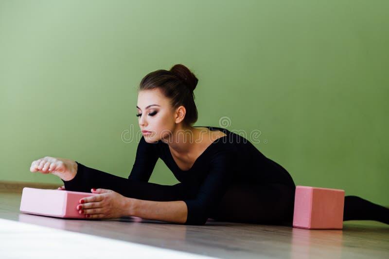 La belle fille moderne élégante de danseur classique avec le corps parfait s'assied sur le plancher dessus sur la ficelle images stock