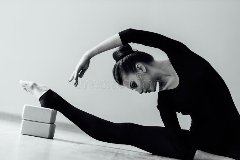 La belle fille moderne élégante de danseur classique avec le corps parfait s'assied sur le plancher dessus sur la ficelle photos stock