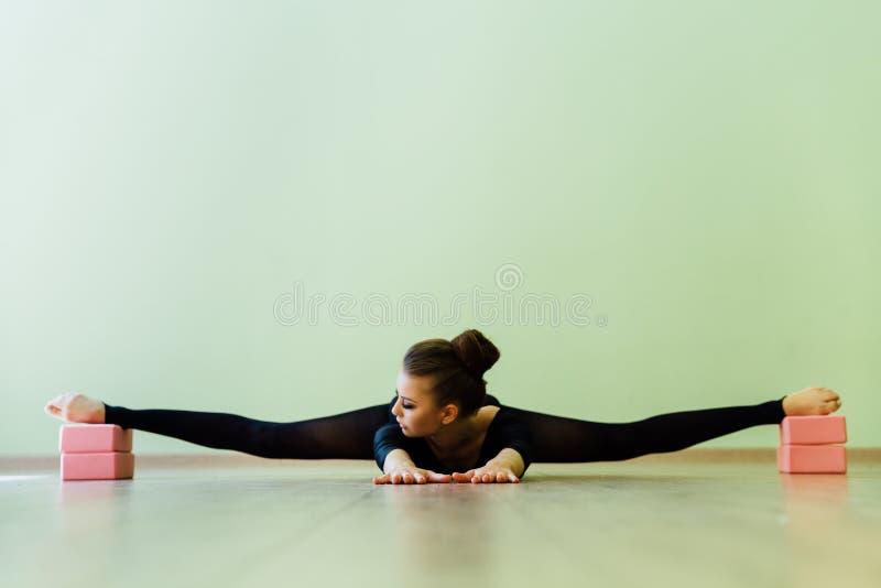 La belle fille moderne élégante de danseur classique avec le corps parfait s'assied sur le plancher dessus sur la ficelle photo libre de droits