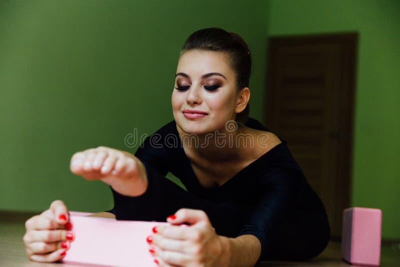 La belle fille moderne élégante de danseur classique avec le corps parfait s'assied sur le plancher dessus sur la ficelle photos libres de droits