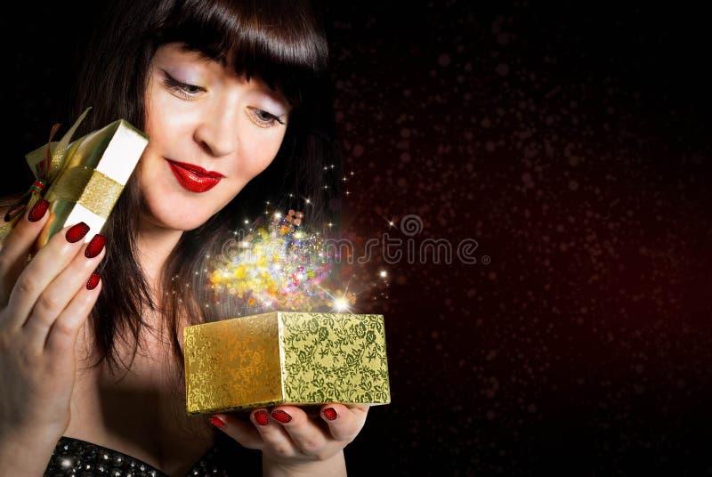La belle fille ouvre un cadeau dans une petite case image stock