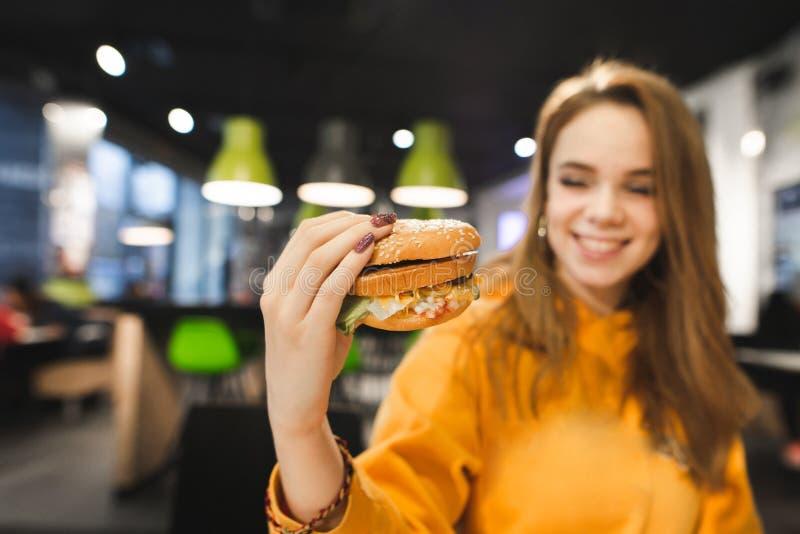 La belle fille positive s'assied dans le restaurant d'aliments de préparation rapide, tient le grand hamburger savoureux à dispos photographie stock