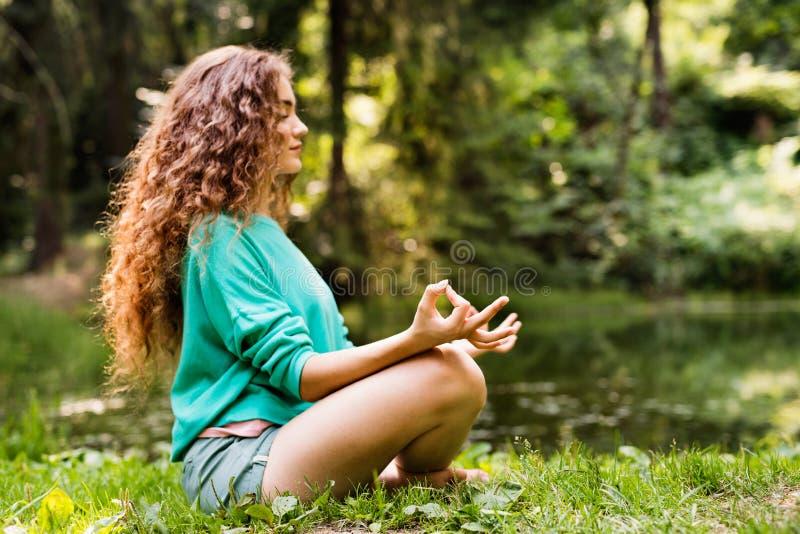 La belle fille pratique le yoga dans la forêt de matin image stock