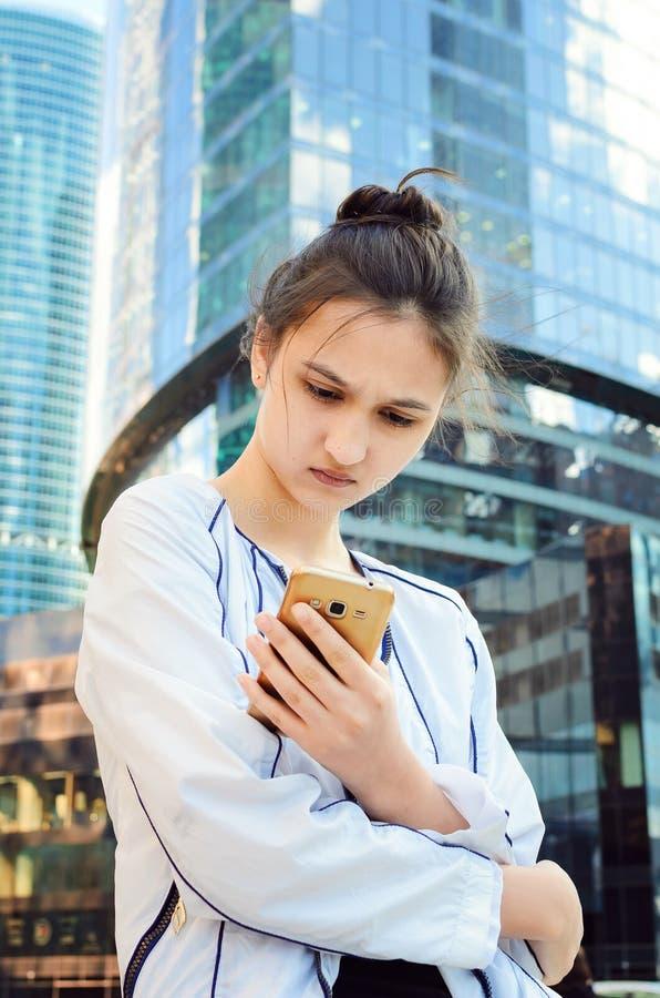 La belle fille regarde dans un téléphone portable images libres de droits
