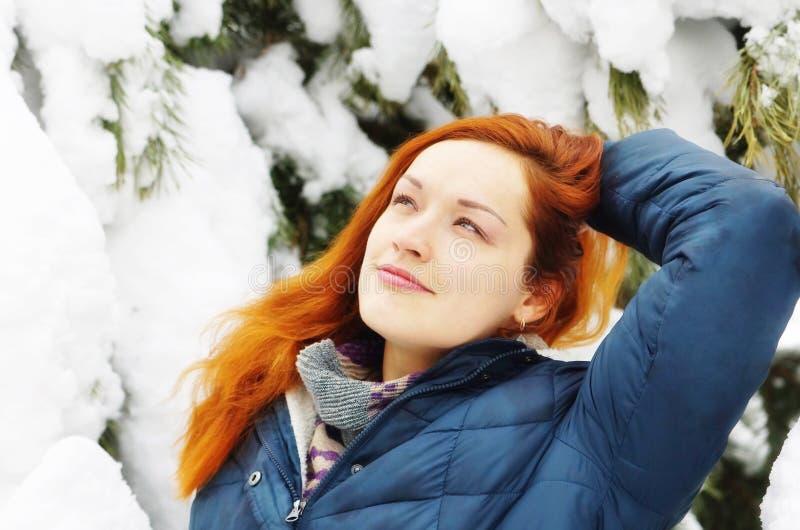 La belle fille rousse heureuse a un repos dans la forêt neigeuse de pin photos stock