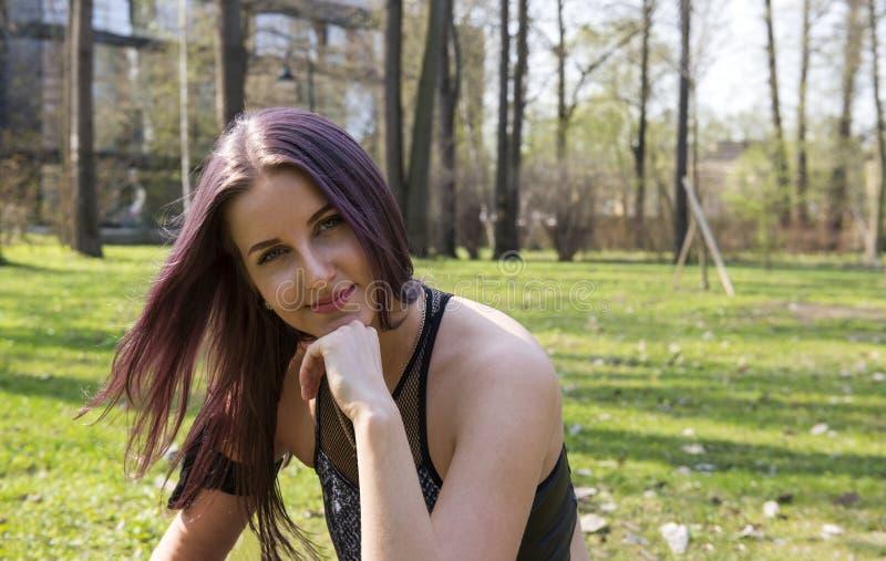 La belle fille s'asseyant sur un pré vert au printemps, se ferment vers le haut du portrait photo stock