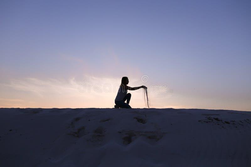 La belle fille s'assied à l'acroupissement sur la colline arénacée de désert sur le coucher du soleil image stock
