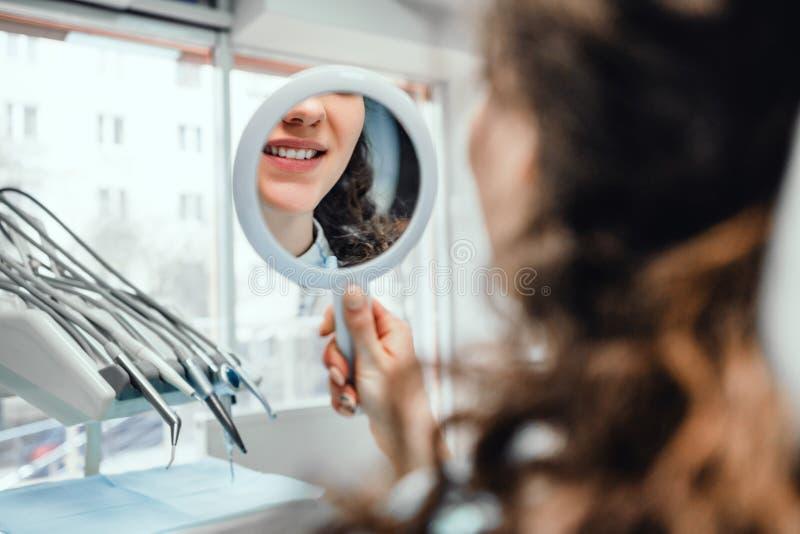 La belle fille s'assied dans la chaise du dentiste et regarde elle-même dans le miroir Fermez-vous vers le haut de la vue photos stock