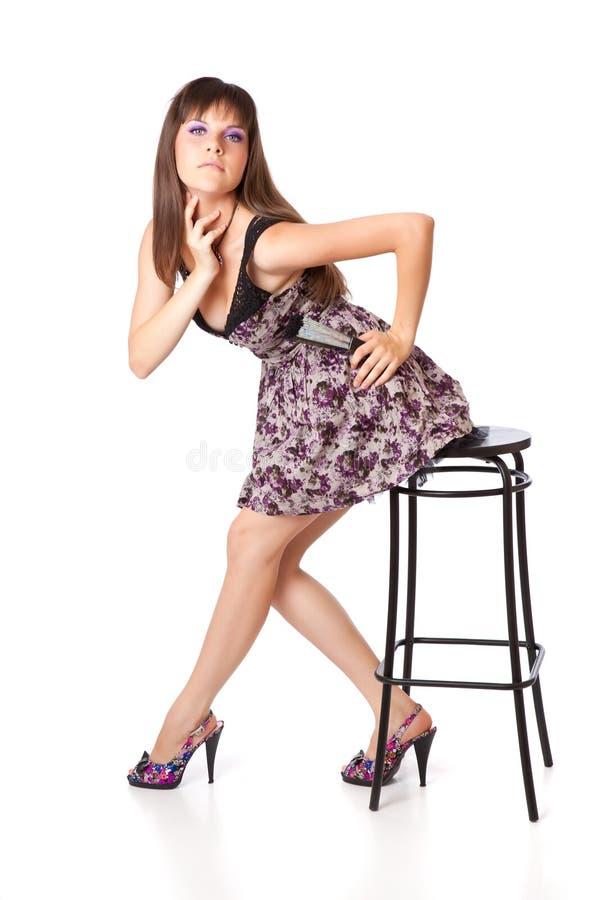 La belle fille s'assied sur un tabouret photo libre de droits