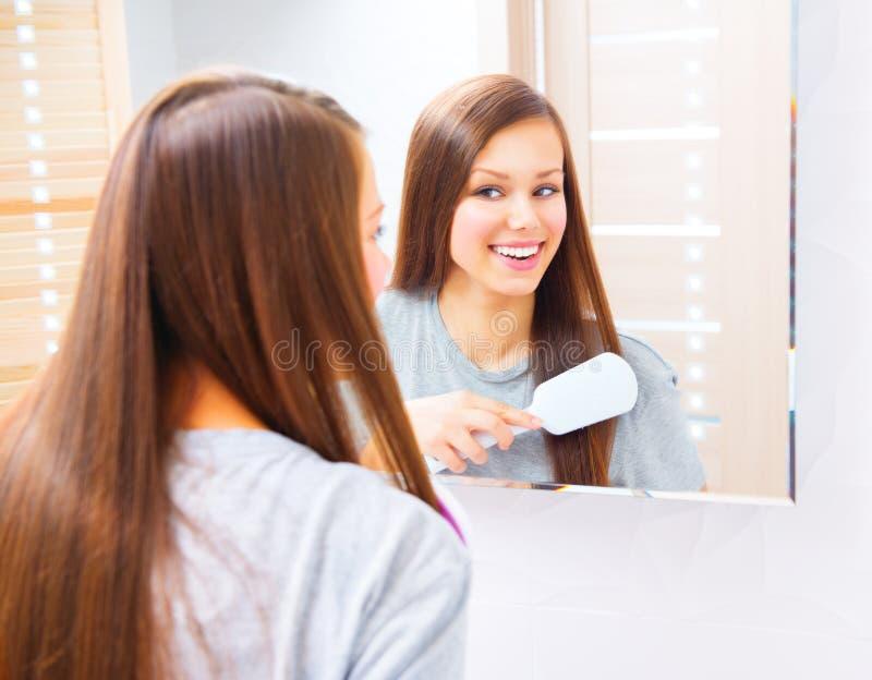 La belle fille se peigne les longs cheveux soyeux images stock