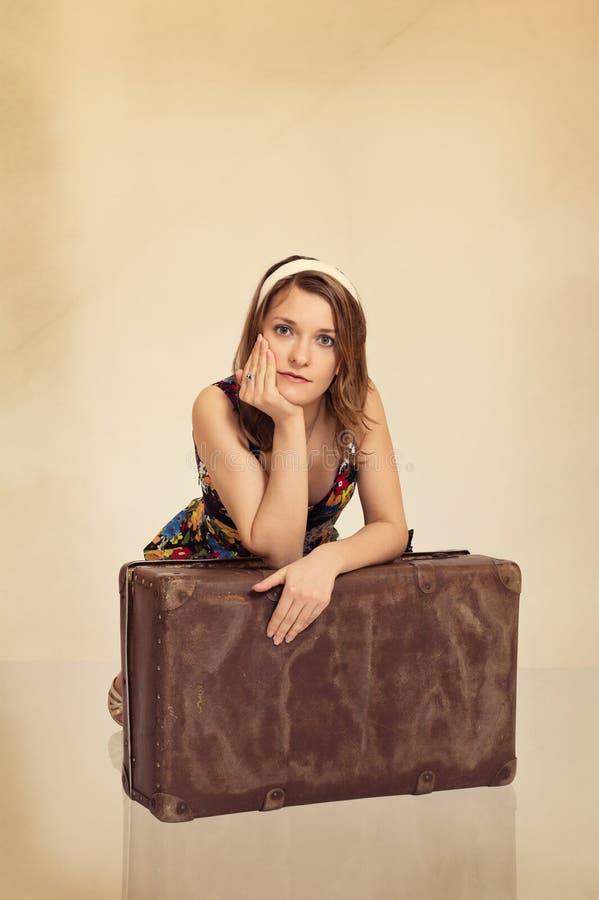 La belle fille se penchant sur la vieille valise a modifié la tonalité dans le rétro type image libre de droits
