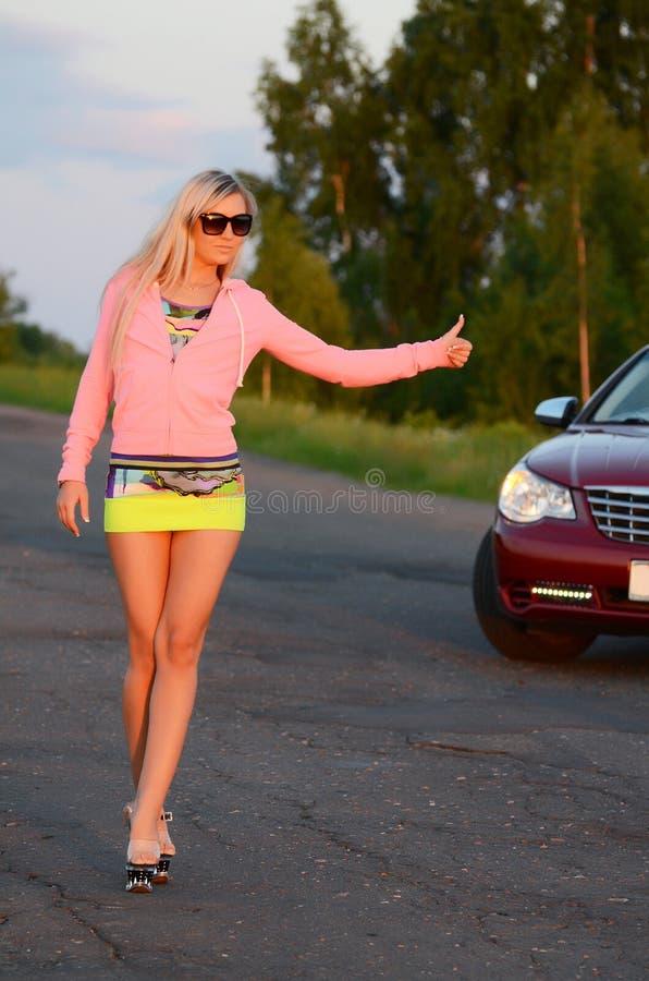 La belle fille se tient près à la voiture rouge photos libres de droits