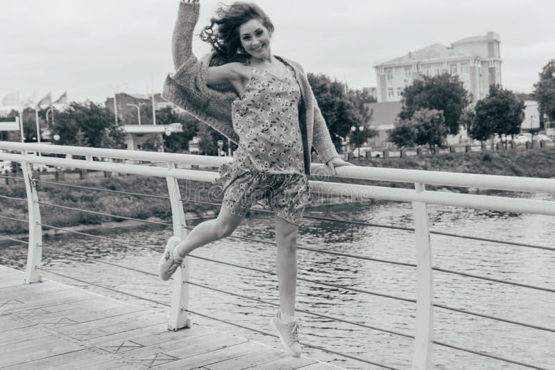 La belle fille se tient sur le pont, le vent souffle dans son visage, développant ses cheveux Sourires de fille photo noire et bl images libres de droits