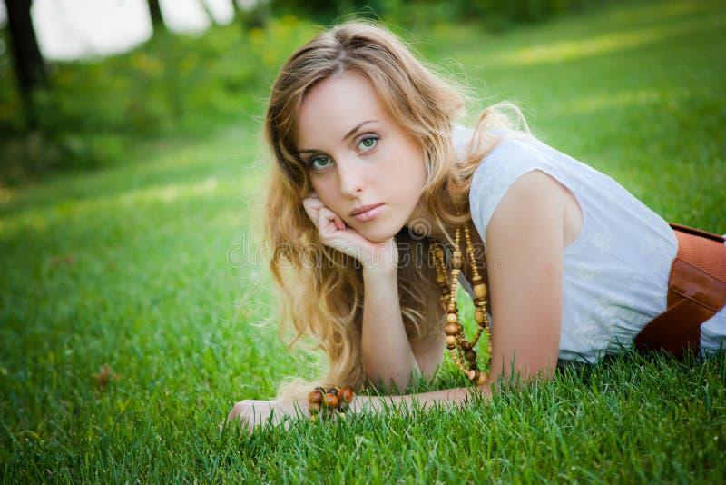 La belle fille se trouve sur l'herbe images stock