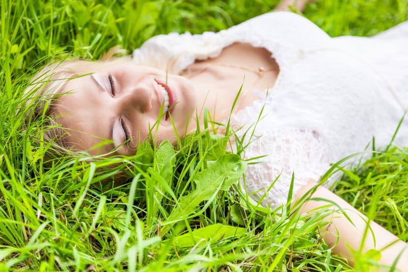 La belle fille se trouve sur l'herbe verte image libre de droits