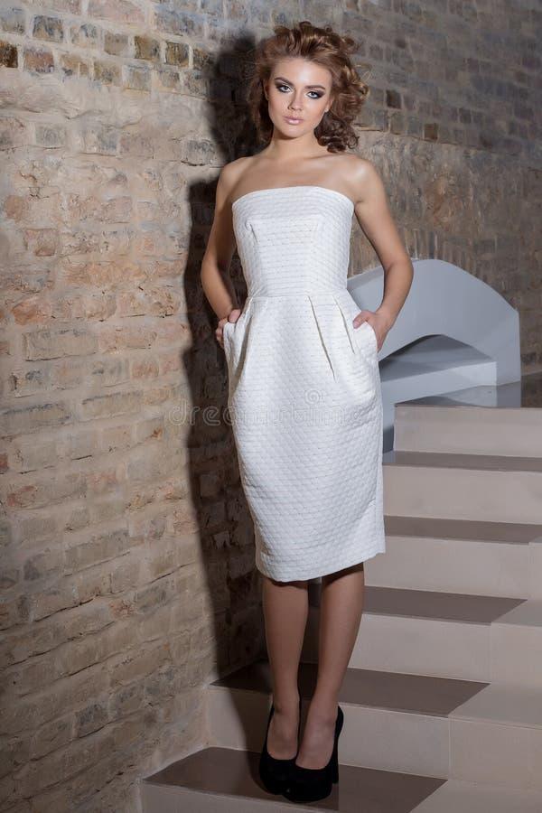 La belle fille sexy élégante avec la belle coiffure et la soirée lumineuse préparent dans la robe blanche de soirée et les chauss images stock