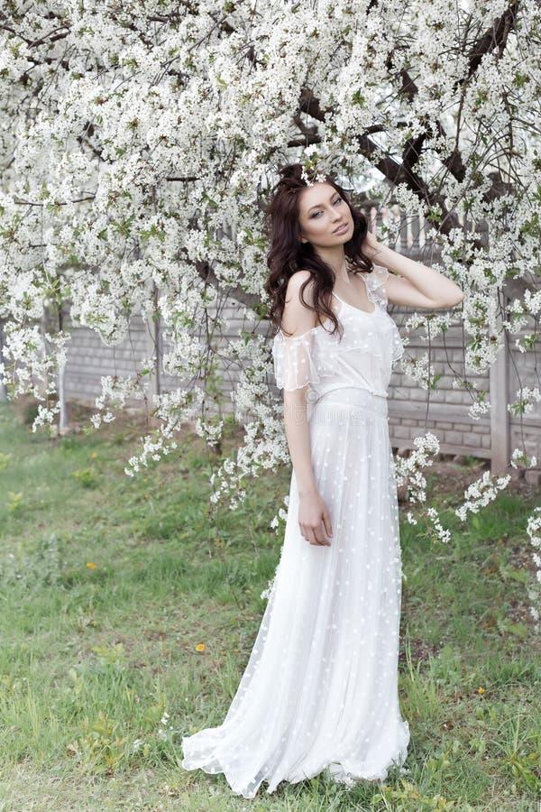 La belle fille sexy avec la longue robe légère de maquillage doux parmi les arbres fleurissants marche au printemps jardin sur un photo libre de droits