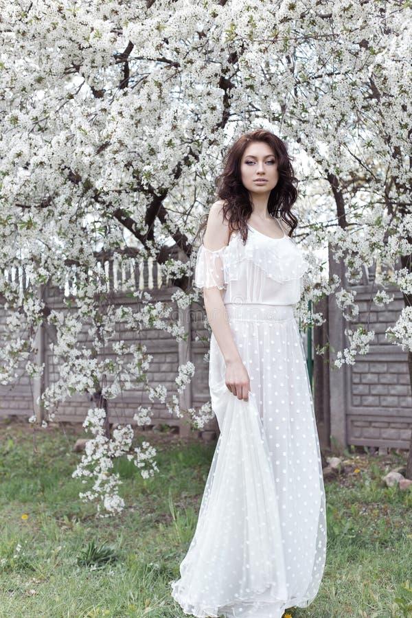 La belle fille sexy avec la longue robe légère de maquillage doux parmi les arbres fleurissants marche au printemps jardin sur un image stock